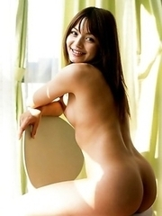 Tina Yuzuki is holding flowers in front her hairy pussy